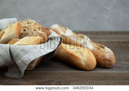 Chopped Baguette In A Wooden Wicker Basket For Bread On An Old Rustic Table. Nearby Are Two Baguette