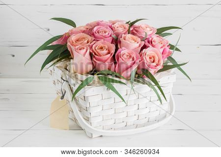 White Basket With Beautiful Pink Roses, On A White Wooden Background.