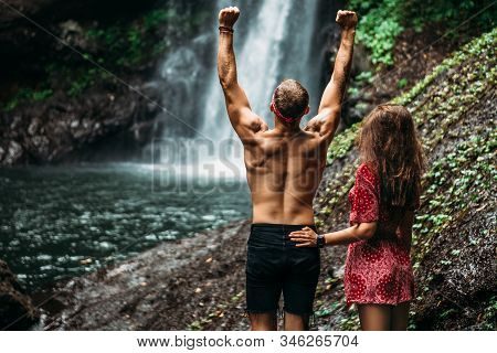 Couple At The Waterfall, Rear View. Honeymoon Trip. Couple On Vacation In Bali. A Couple In Love Tra