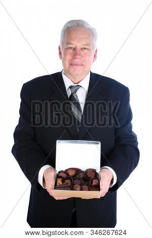Valentines Day. Man in a suit holds a box of assorted exotic chocolates. Isolated on white. Room for text. Clipping Path. People world wide love chocolates. Chocolate is enjoyed for holidays.