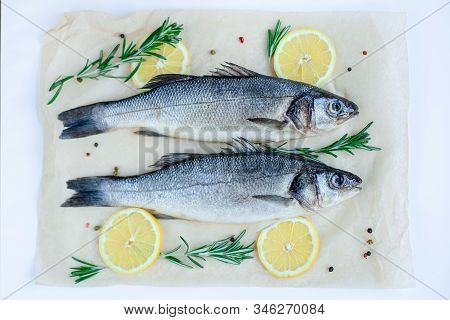 Raw Sea Bass With Spices And Herbs On A White Slate Table. Fresh Sea Bass.