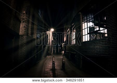 London Alley In Dark Night With Street Lamp Reflection