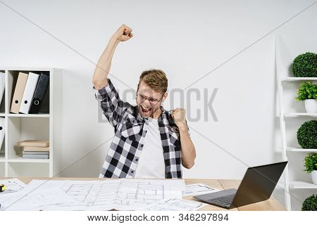 Successful And Excited Young Adult Architect Freelancer Celebrating Triumph After Working In Profess