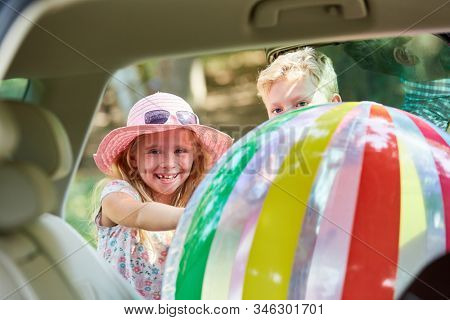 Children stow a big colorful ball in the back seat in the car before traveling