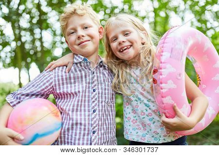 Happy siblings couple in summer vacation with ball and swimming ring