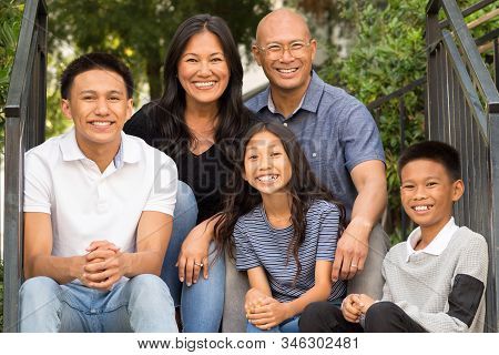 Portrait Of An Asian Family Laughing And Talking Outside.