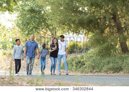 Happy Asian Family Walking And Talking Outside.