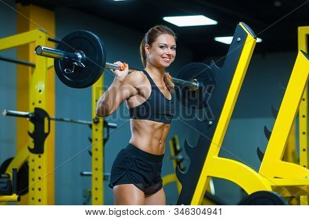 Photo Of A Smiling Woman Holding Weight While Working Out With Barbell In A Gym. Muscles Woman Showi