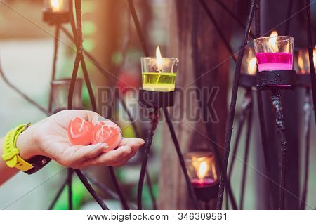 A Red Heart Shaped Candle In A Woman's Hand With Candlelight In Many Small Glass Cups. A Valentine's