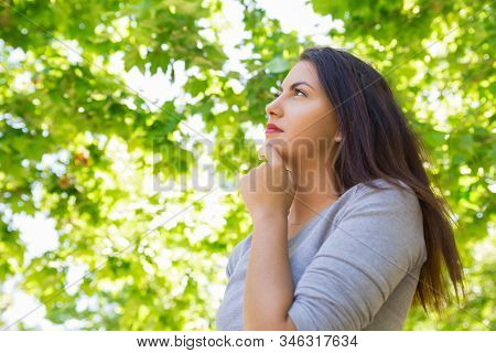 Thoughtful Young Woman Holding Hand On Chin. Low Angle Shot Of Attractive Young Lady Daydreaming In