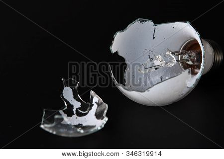 Broken Light Bulb Isolated On Black Background With Shattered Piece Of Lightbulb. Technology Concept