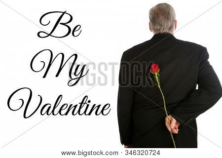 Man with a Single Red Rose. A man in a suit has a Red Long Stem Rose behind his back as a surprise gift.