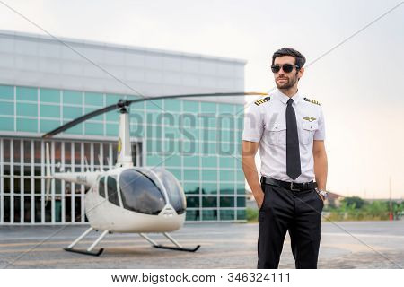 Portrait Of Handsome Commercial Pilot In Captain White Uniform Standing And Looking Smart Near Small