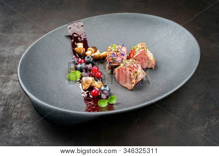 Fried dry aged venison tenderloin fillet medallion steak natural with mushrooms and forest berries as closeup on a modern design plate