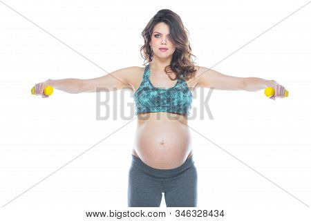 Pregnant Woman Training With Dumbbells To Stay Active. Pregnant Woman Practicing Fitness And Working