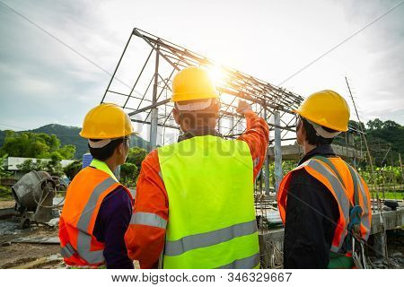 Engineer Technician Watching Team Of  Worker Control In Construction Workers Wearing Safety Clothing