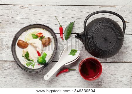 Tom Kha traditional Thai soup with chicken, mushrooms, coconut milk and hot spices. With green tea pot and bowl. Top view