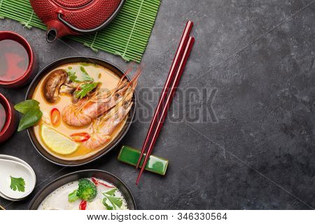 Tom Yum and Tom Kha traditional Thai soups with seafood, chicken, mushrooms, coconut milk and hot spices. With green tea pot and bowl. Top view with copy space