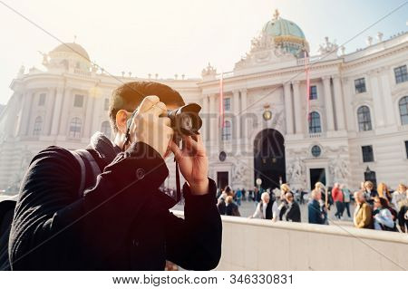 Young Asian Man Tourist Taking Photos With Camera In Hands Near Hofburg Palace In Vienna, Austria, E