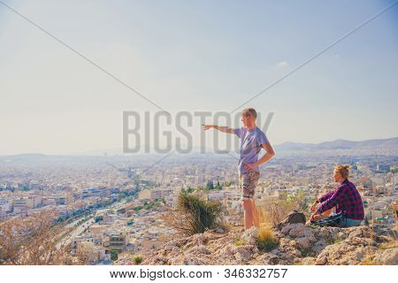 Couple Man And Woman On Top Of Mountain Enjoying Beautiful Landscape Cityscape Athens Greece On Back