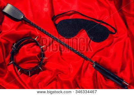 Bondage, Kinky Adult Sex Games, Kink And Bdsm Lifestyle Concept With A Whip, Collar, Eye Mask On Red