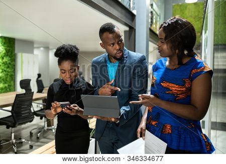 Three Black African Colleagues Walking Through Coworking Workspace Strategizing On Their Way To Boar