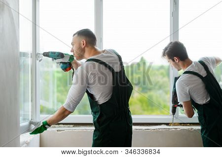 Two Workers Are Mounting A Window In The House