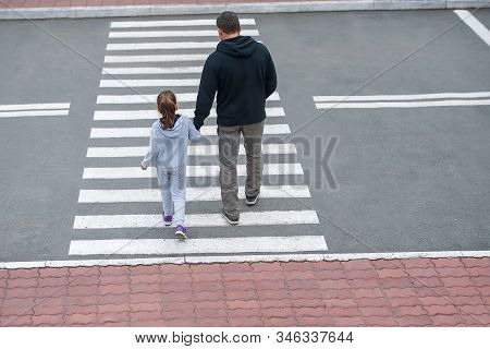 A Man And A Small Child On A Zebra Crossing Trespassing By Crossing The Street. In The Summer On The