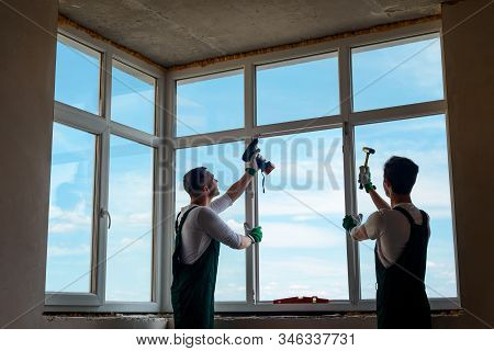 Shot Of Two Workers Installing A Window In A New Building