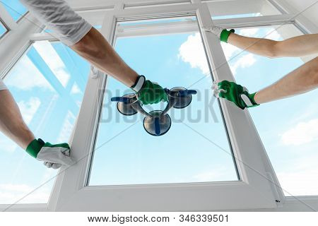 Holding Glass With A Vacuum Lifter. Two Guys Installing A Window