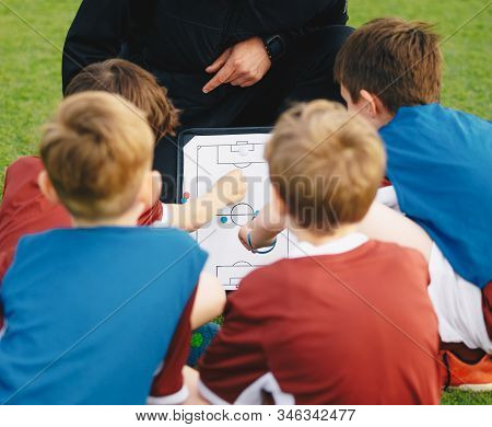 Coach Teaching Kids On Soccer Training Unit. Young Boys Sitting Together With Coach On Grass Pitch.