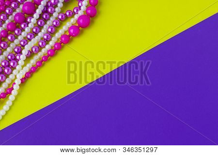 Mardi Gras Or Fat Tuesday Composition. Multi Colored Mardi Gras Beads On Yellow And Purple Paper Bac