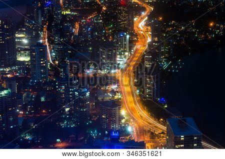 Aerial Urban Night Traffic With Busy Highway. Modern City Infrastructure, Commercial District. Gold