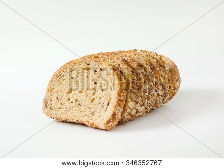 Sliced loaf of whole grain bread, crust topped with rolled oats and seeds (flax, sesame, sunflower)
