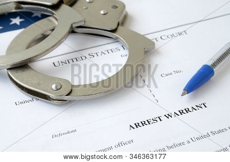 District Court Arrest Warrant Court Papers With Handcuffs And Blue Pen On United States Flag. Concep