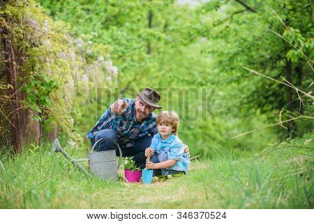 Father And Son In Cowboy Hat On Ranch. Eco Farm. Small Boy Child Help Father In Farming. Watering Ca
