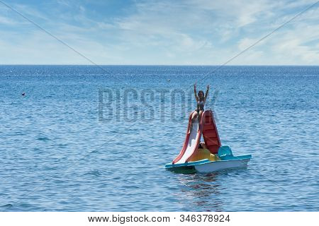 Teen In Bathing Suit Sitting With Hands Up In The Air On Paddleboat With Slide At Beach In Eressos,