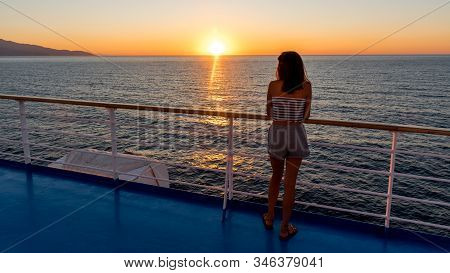 Asian Teen In Tube Top Standing On Deck Of Ferry Looking At Sunset On Ferry To Lesvos