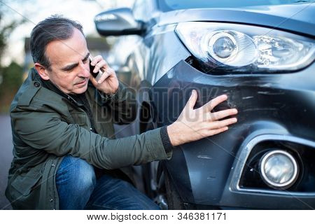 Unhappy Mature Male Driver With Damaged Car After Accident Calling Insurance Company On Mobile Phone