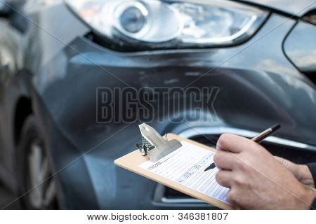 Close Up Of Auto Workshop Mechanic Inspecting Damage To Car And Filling In Repair Estimate