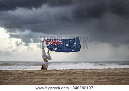 Australian Flag Blowing In The Wind Hanging By The Feet Of Female Yogi Doing A Headstand Pose On A A
