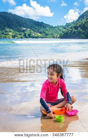 Little Girl Playing With Sand On Maracas Bay Beach Trinidad And Tobago Sitting Outdoors Fun Activity