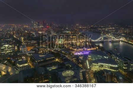 Night Aerial View Of Tower Bridge And City Of London, England. Smog Over City Reduces View Distance.