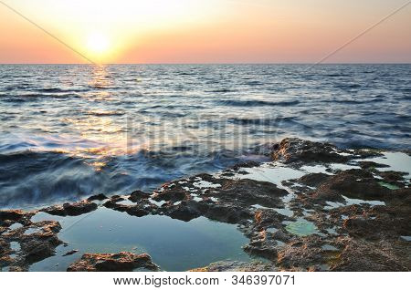 Beautiful Pink Sunset And Water Stones Over Black Sea Rocky Coastline In Crimea