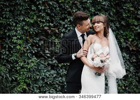 Amazing Smiling Wedding Couple. Pretty Bride And Stylish Groom. Groom And Bride Posing In Front Wall