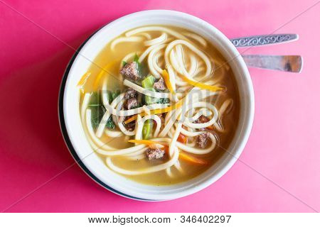 A Bowl Of Asian Noodle Soup Served With Meat And Vegetables