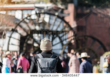 Young Man Traveler Traveling At Giant Water Wheels In Lijiang Old Town, Landmark And Popular Spot Fo