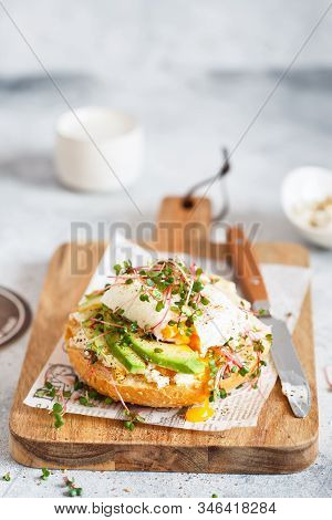 Poached Egg With Avocado, Ricotta Cheese And Radish Sprouts On Burger Bun. Healthy Sandwich With Bre