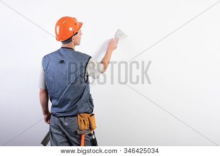 The Builder Smoothes The Wall With A Spatula. In Work Clothes And Hard Hat. On A Light Gray Backgrou
