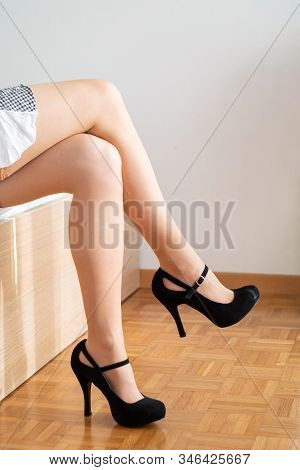 Caucasian Woman In Sexy Stocking Short Skirt And Black Shoes Standing On The Edge Of A Bed Legs Cros